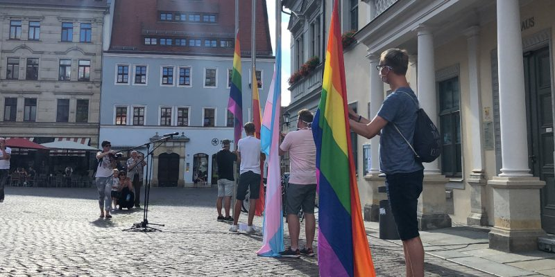 Neben den zwei Regenbogenflaggen und der Trans Pride Flag wurde die Stadtflagge von Pirna gehisst. Gemeinsam zieren die vier Banner nun eine Woche lang das Rathaus und den Marktplatz.